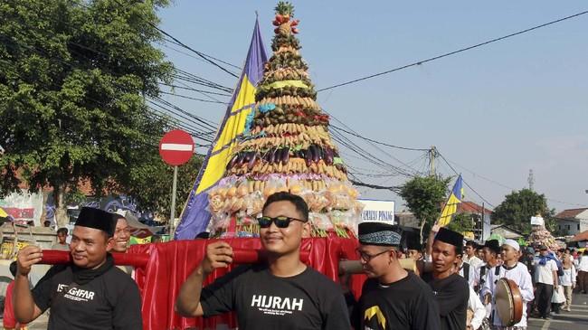 Peserta membawa gunungan makanan dan hasil bumi pada pelaksanaan Kirab Maulid 1441 H di Kampung Berkelir Tangerang, Banten, Jumat (8/11). Acara yang dihadiri ribuan umat muslim se-Tangerang ini diadakan dalam rangka memperingati Maulid Nabi Muhammad SAW. (ANTARA FOTO/Muhammad Iqbal)