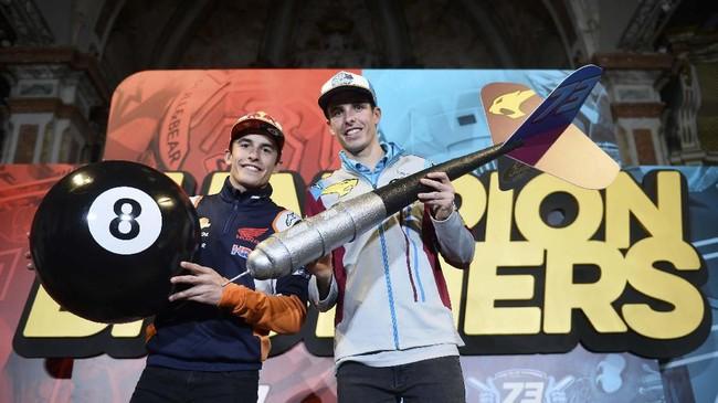 Marc Marquez (kiri) memegang bola 8 sebagai penanda gelar juara dunia yang pernah diraihnya, sementara Alex memegang dart. (JOSE JORDAN / AFP)