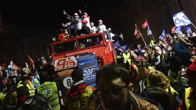 Marc Marquez dan Alex Marquez diarak menggunakan bus atap terbuka. Ini adalah kali kedua setelah musim 2014 Marc dan Alex sama-sama merebut gelar juara dunia Grand Prix. (JOSE JORDAN / AFP)