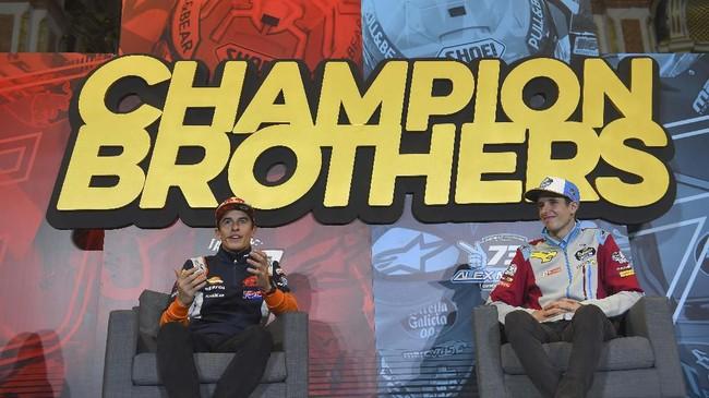 Marc Marquez (kiri) dan sang adik, Alex, menjalani konferensi pers jelang perayaan gelar juara dunia MotoGP dan Moto2 2019 di Cervera. (JOSE JORDAN / AFP)