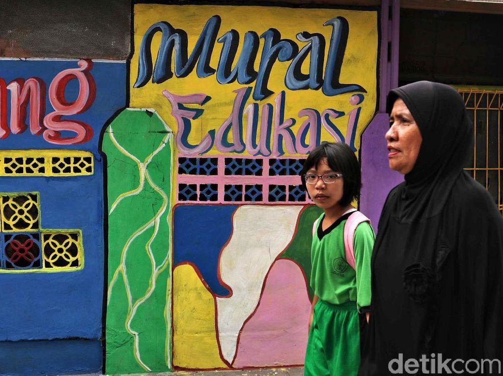 Dua orang warga melintas di depan mural edukasi di kawasan RW 8, Lagoa, Koja, Jakarta Utara.