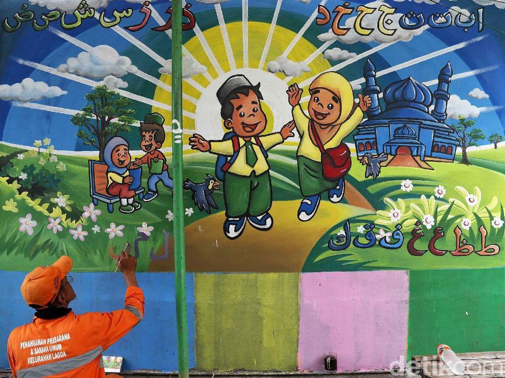 Petugas PPSU membuat mural di kawasan RW 8, Lagoa, Koja, Jakarta Utara, Selasa (12/11/2019).