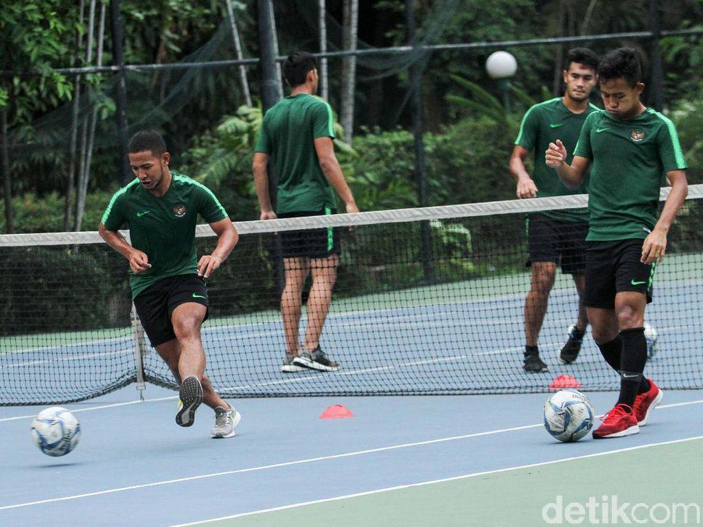 Pemain berlatih ringan seperti menggiring bola menyundul di lapangan tenis.
