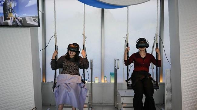 Di Sky Circus Sunshine 60, pengunjung bisa mencoba bermain ayunan sambil mengenakan kacamata teknologi virtual reality. Kacamata tersebut memperlihatkan pemandangan di luar ruangan, sehingga pengunjung seakan bermain ayunan di langit Jepang. (AP Photo/Jae C. Hong)