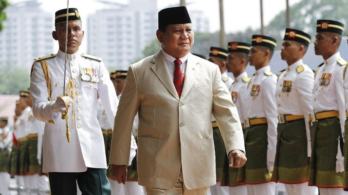 Indonesian Defense Minister Prabowo Subianto, front right, salutes near Malaysian counterpart Mohamad Sabu, second left, as he inspects honor guard at Malaysia Defense Ministry in Kuala Lumpur, Thursday, Nov. 14, 2019. (AP Photo/Vincent Thian)