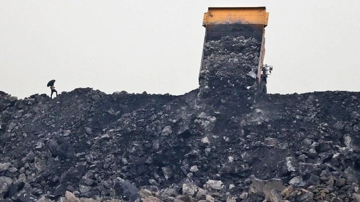 In this Oct. 23, 2019, photo, a laborer keeps watch as coal is unloaded from a truck in the village of Rajapur in Jharia, a remote corner of eastern Jharkhand state, India. The fires started in coal pits in eastern India in 1916. More than a century later, they are still spewing flames and clouds of poisonous fumes into the air, forcing residents to brave sizzling temperatures, deadly sinkholes and toxic gases. (AP Photo/Aijaz Rahi)