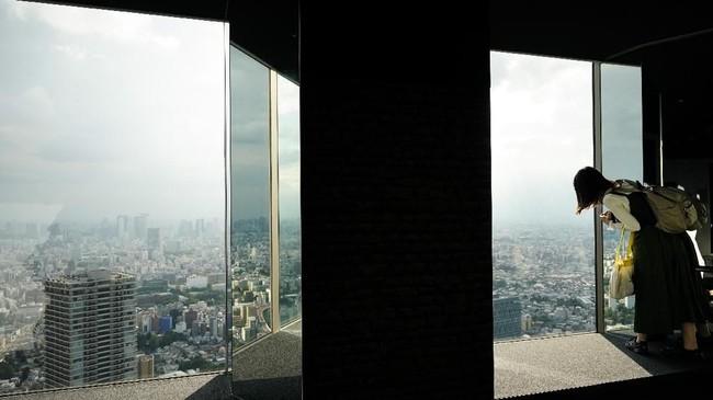 Seorang pengunjung wanita melihat pemandangan dari jendelaruang observasi Sky Circus Sunshine 60 di Tokyo, Jepang. (AP Photo/Jae C. Hong)