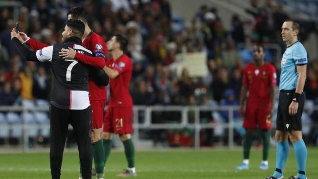 Dalam laga tersebut, sempat ada penyusup yang akhirnya bisa foto bersama Cristiano Ronaldo.(AP Photo/Armando Franca)