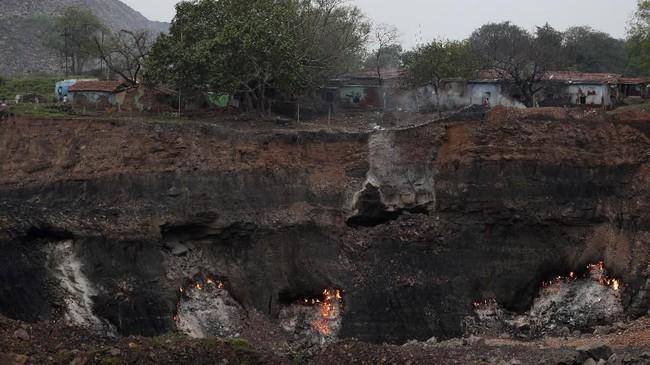 Sebuah tambang batu bara di Jharia, India terus memuntahkan api dan awan asap beracun.(AP Photo/Aijaz Rahi)