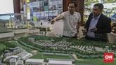 Seorang pengunjung yang penasaran melihat maket mengenai peluang lokasi properti yang dipamerkan dalam pameran di JCC, Jakarta.(CNN Indonesia/Bisma Septalism)