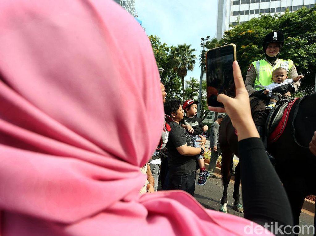 Polisi berkuda menjadi pusat perhatian warga, terutama anak-anak.