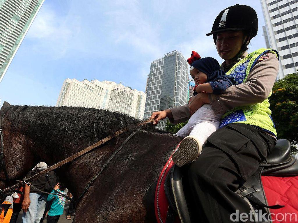 Polisi melayani anak-anak yang ingin menaiki kuda.