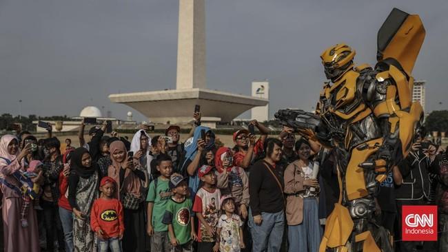 Anak-anak kecil mengamati Transformer berukuran besar yang berjalan melewati mereka di Lapangan Silang Monas, Jakarta Pusat, Minggu (17/11). (CNN Indonesia/Bisma Septalisma)