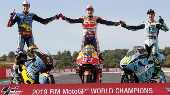 Alex Marquez, Marc Marquez, dan Lorenzo Dalla Porta berpose sambil berdiri di atas sepeda motor. (AP Photo/Alberto Saiz)