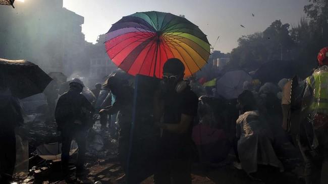 Polisi anti huru-hara menerobos salah satu pintu masuk di tengah kobaran api di bagian dalam dan luar kampus sebelum matahari terbit.(AP Photo/Kin Cheung)