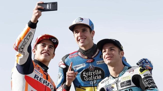 Marc Marquez, Alex Marquez, dan Lorenzo Dalla Porta melakukan selfie jelang balapan MotoGP Valencia 2019 di Sirkuit Ricardo Tormo, Minggu (17/11). (AP Photo/Alberto Saiz)