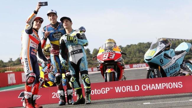 Marc Marquez, Alex Marquez, dan Lorenzo Dalla Porta melakukan selfie di depan sepeda motor masing-masing. (AP Photo/Alberto Saiz)