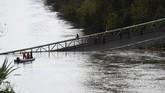 Jembatan ambruk pada pukul 08.00 waktu setempat setelah kabel penghubung jembatan tersebut putus. Akibatnya, tiga kendaraan jatuh ke dalam sungai. (Photo by ERIC CABANIS / AFP)