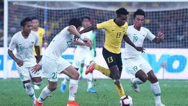 Penyerang Malaysia Mahamadou Sumareh dikawal pemain Timnas Indonesia Bayu Pradana (kanan) dan Hendro Siswanto (kiri) di Kualifikasi Piala Dunia 2022. (Photo by KAMARUL AKHIR / AFP)