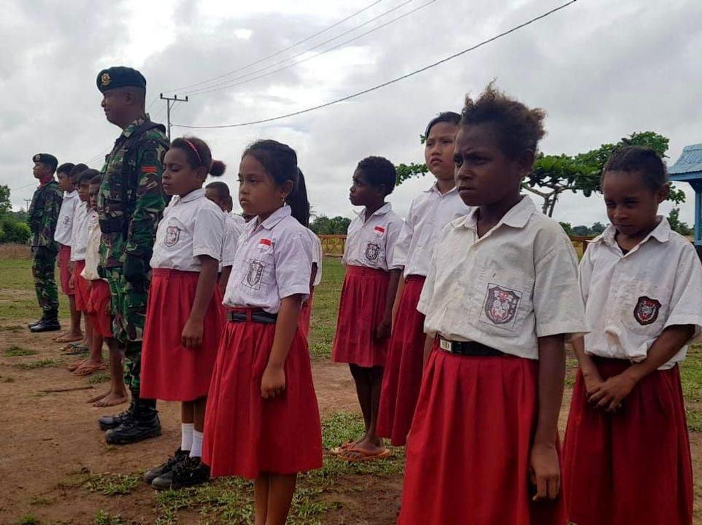 Kegiatan upacara bendera itu digelar guna menanamkan jiwa nasionalisme pada murid-murid sekolah yang berada di perbatasan RI-PNG. Istimewa/Dok. Pasi Intel Satgas Pamtas RI-PNG Yonif 411 Kostrad Lettu Inf Asep Saepudin.