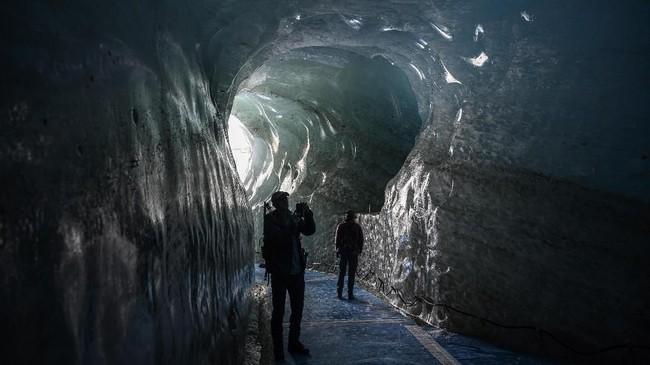 Para pekerjapun sudah menyelimuti bagian atas terowongan es yang ramai dikunjungi di daerah itu denganterpal putihdan batu-batu besardemi melindunginya dari matahari.(Photo by MARCO BERTORELLO /AFP)
