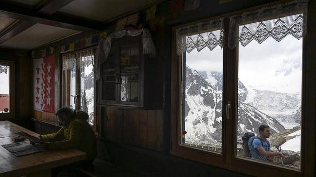 Pemandangan batuan di antara salju dariCouvercle Refuge (mountain hut)di Chamonix. Perubahan akibat pemanasan global itumemicu penampakan batuan dasar, salju dan es yang lebih rapuh, dan pelebaran celah. (Photo by MARCO BERTORELLO / AFP)