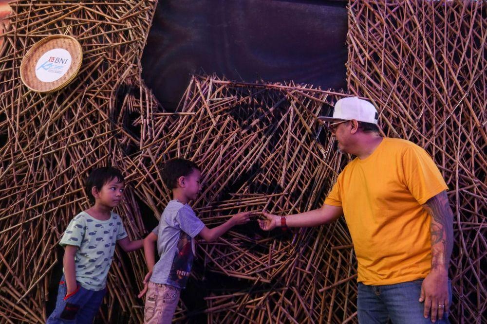 Seniman Nus Salomo (kanan) menjelaskan hasil karyanya kepada anak-anak tentang instalasi bambu berbentuk wajah Ir Soekarno yang dipamerkan pada aksi BNI KEJAR atau Kenali Sejarah Raihlah Mimpimu di Terowongan Dukuh Atas, Jakarta, Minggu (24 November 2019). Aksi BNI KEJAR kali ini digelar dalam rangka memperingati Hari Kesehatan & Hari Pahlawan Nasional selama sepekan mulai 24 November hingga 1 Desember 2019. (dok: BNI)