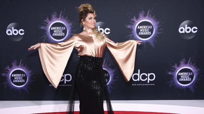 Shania Twain memilih busana yang tak sesuai dengan dirinya. Dia terlihat seperti piala Oscar's dengan warna gold dan hitam (Rich Fury/Getty Images/AFP)