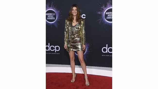 Cobie Smulders memilih busana bergaya formal, tapi dia memilih warna metalik emas (Photo by Jordan Strauss/Invision/AP)