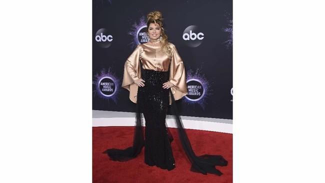 Shania Twain juga memilih atasan berwarna emas. Namun dia meredam warna emasnya dengan warna hitam. (Jordan Strauss/Invision/AP)