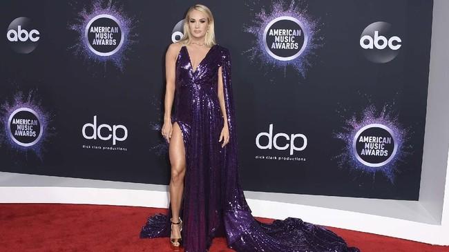 Carrie Underwood memilih gaun berwara ungu metalik dengan cape dan high slit.(Jordan Strauss/Invision/AP)