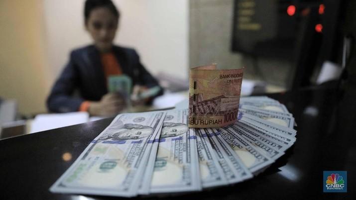 Nilai tukar rupiah terhadap dolar AS melemah di kurs tengah BI. Rupiah juga menghuni zona merah di perdagangan pasar spot.