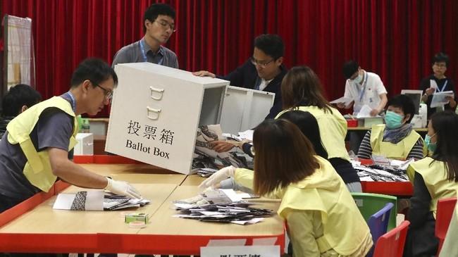 Para kandidat calon anggota dewan unggul lebih dari setengah dari 452 daerah pemilihan melawan kandidat pro pemerintah China. (AP Photo/Ng Han Guan)