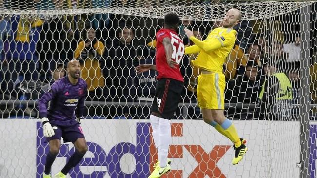 Bek Manchester United Di'Shon Bernarddan gelandang Astana Ivan Maevski duel udara. Setan Merah kalah 1-2 dari Astana diAstana Arena, salah satunya karena gol bunuh diri Bernard. (Photo by stringer / AFP)