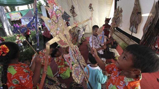 Sejumlah anak-anak bermain wayang kulit bersama dalang di Pendopo Banyuwangi, Jawa Timur, Kamis (2/11). (ANTARA FOTO/Budi Candra Setya)