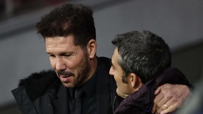 Pelatih Atletico Madrid Diego Simeone (kiri) berbicara dengan pelatih Barcelona Ernesto Valverde sebelum laga Liga Spanyol di Stadion Wanda Metropolitano, Minggu (1/12) malam waktu setempat. (AP Photo/Manu Fernandez)