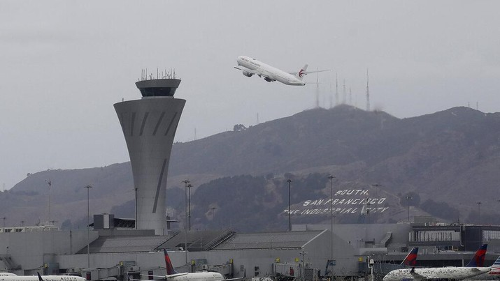 A plane takes off behind the air traffic control tower at San Francisco International Airport in San Francisco, Tuesday, Nov. 26, 2019. Northern California and southern Oregon residents are bracing for a 'bomb cyclone' that's expected at one of the busiest travel times of the year. (AP Photo/Jeff Chiu)