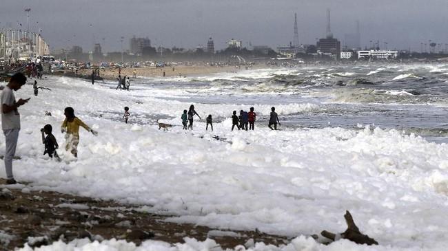 Warga berbondong-bondong ke pantai menyaksikan beberapa lapisan zat seperti busa di sepanjang garis pantai Marina, Chennai. (AP Photo/R.Parthibhan).