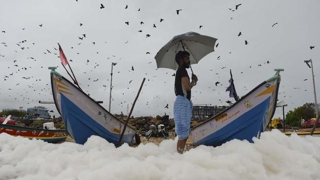 Seorangpria melihatbuih berbusa yang disebabkan oleh polutan di ombak Pantai Marina, Chennai pada awal Desember 2019. (Photo by Arun SANKAR/AFP).