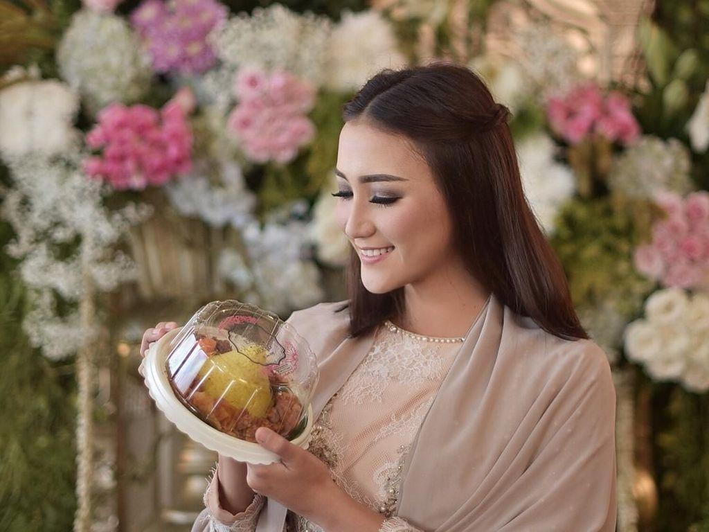 Erica ini punya badan yang langsing dan ideal padahal aslinya suka makan dan ngemil. Lihat saja aksinya saat menunjukkan seporsi nasi tumpeng mini yang siap jadi santapannya. Foto: instagram @ericaputrii