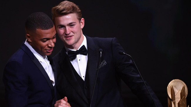 Pemain Juventus dan timnas Belanda Matthijs de Ligt meraih penghargaan trofi Kopa yang diberikan oleh penyerang Paris Saint-Germain, Kylian Mbappe saat penghargaan Ballon d'Or 2019. (Photo by FRANCK FIFE / AFP)