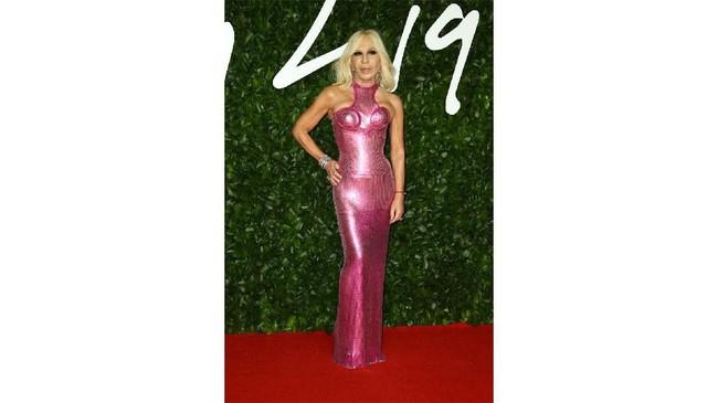 Desainer Donatella Versace tampil dengan gaun pas badan berwarna pink metalik dan bercorak garis-garis. Namun, corak itu justru membuat perancang asal Italia ini seperti dililit karpet. (Photo by Joel C Ryan/Invision/AP)
