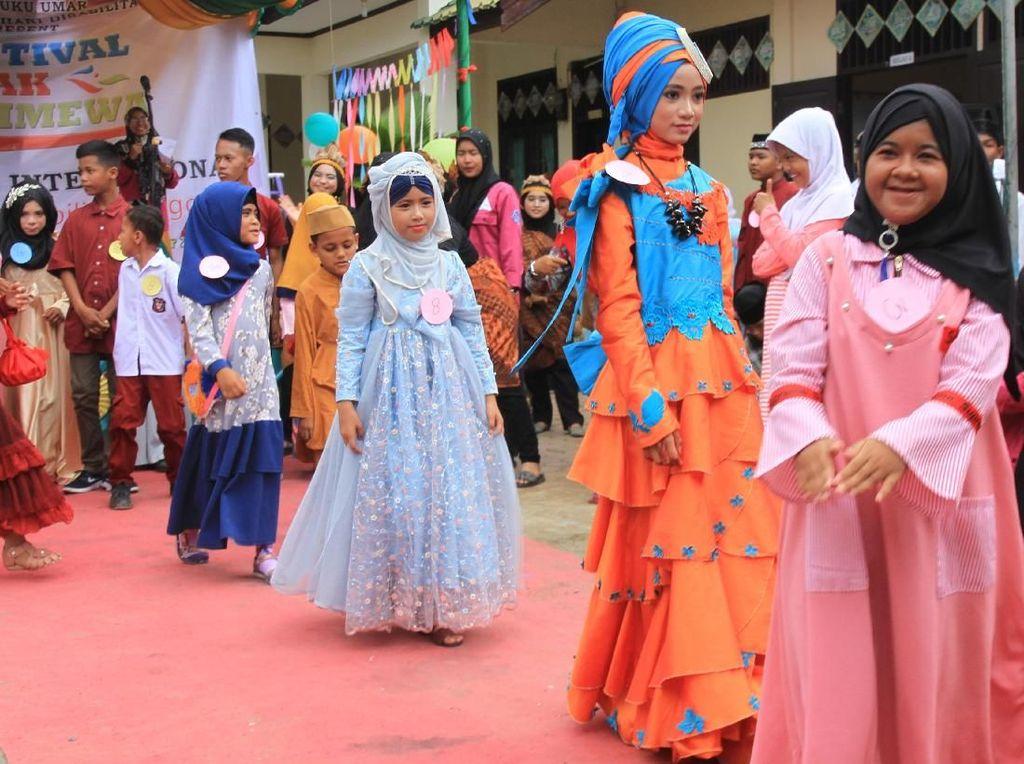Sejumlah siswa penyintas tunarungu dan penyintas tunawicara mengikuti peragaan busana pada acara festival anak istimewa di Sekolah Menengah Pertama Luar Biasa (SMPLB) Negeri Meulaboh, Aceh Barat, Aceh, Selasa (3/12/2019). Festival anak istimewa yang diikuti 86 siswa dari Sekolah Dasar Luar Biasa (SDLB) Nagan Raya dan Sekolah Menengah Pertama Luar Biasa (SMPLB) Meulaboh tersebut serangkaian kegiatan dalam peringatan Hari Disabilitas Internasional 2019 dengan mengusung tema Indonesia Inklusi Disabilitas Unggul. Antara Foto/Syifa Yulinnas.