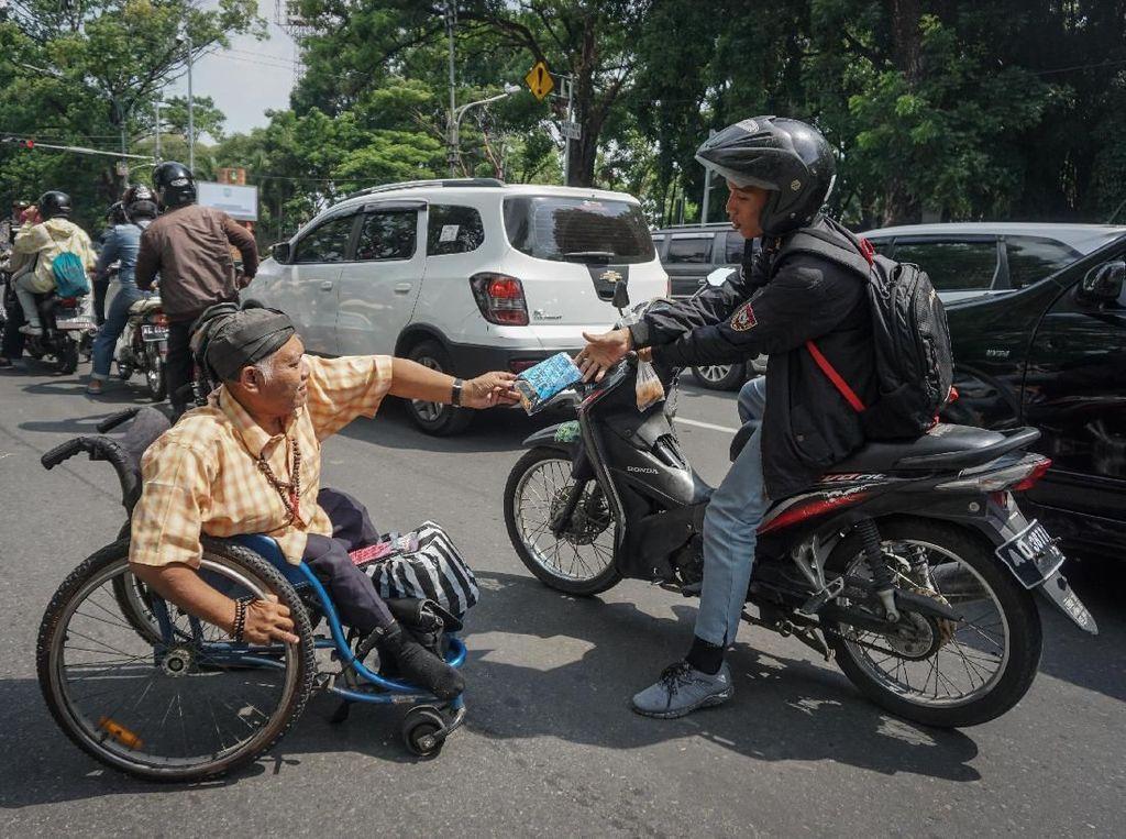 Para penyintas disabilitas di Solo punya cara yang menarik untuk memperingati Hari Disabilitas Internasional. Mereka membagikan souvenir hasil kerajinan tangan kepada para pengguna jalan di kawasan Jalan Slamet Riyadi, Solo, Jawa Tengah, Selasa (3/12/2019). Antara Foto/Mohammad Ayudha.