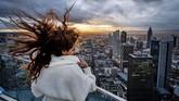 Rambut melambai seorang turis muda Prancis di platform Main Tower di Frankfurt, Jerman saat matahari terbenam, Kamis (28/11). (AP Photo/Michael Probst)