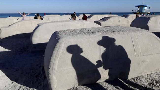 Warga tengah berjalan di 'mobil pasir' hasil perupa Leandro Erlich di Pantai Miami, Argentina pada Selasa (3/12) untuk menarik perhatian isu perubahan iklim dan kenaikan air laut. (AP Photo/Lynne Sladky)