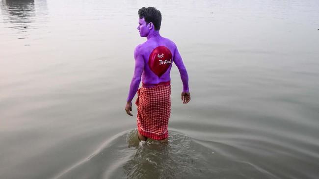 Seorang sukarelawan menceburkan dirinya ke sungai untuk membasuh cat yang ada di tubuhnya terkait dengan peringatah Hari AIDS Dunia pada Kolkata, Sabtu (30/11). (Photo by Dibyangshu SARKAR / AFP)