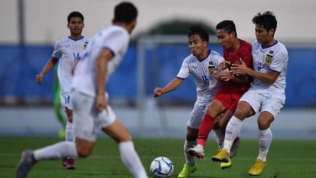 GelandangTimnas Indonesia Evan Dimas (kedua kanan) diapit dua pemain Timnas Laos Somlith Sengvanny (ketiga kanan) dan Somxay Keohanam (kanan). (ANTARA FOTO/Sigid Kurniawan/wsj)