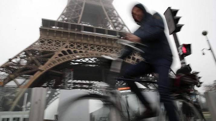A woman walks her dog on the empty Champs Elysees avenue, with the Arc de Triomphe in background, in Paris, Thursday, Dec. 5, 2019. The Eiffel Tower shut down Thursday, France's vaunted high-speed trains stood still and teachers walked off the job as unions launched nationwide strikes and protests over the government's plan to overhaul the retirement system. (AP Photo/Francois Mori)