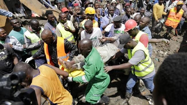 Tim SAR membopong seorang yang dievakuasi dari runtuhan bangunan enam lantai di Tasia Embakasi, Kenya, Jumat (6/12). (AP Photo/Khalil Senosi)